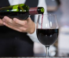 Mid section of bartender pouring red wine on glass in bar counter